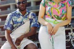 Anicia, wearing a 90's pink tropical shirt, 80's washed out denim patched shorts, lime green vinyl belt. Tahir, wearing blue 70's Hawaiian shirt and overall shorts.
