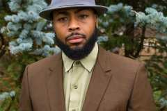 Donny is wearing an 80's brown suit with a pale green button down shirt and vintage grey fedora.