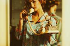 Grace, wearing an 80's striped/floral house dress, talking on vintage rotary phone.