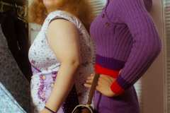 Hailey, wearing a 70's floral wrap dress with purple detail. Grace, wearing a purple knit 60's mod dress, posing with vintage Samsonite luggage bag.