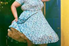 Hailey, wearing a floral blue dress with crinoline, vintage head-piece and metallic pumps.
