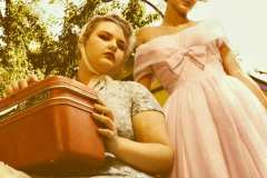 Hailey, wearing floral dress with crinoline, paired with vintage headpiece and Samsonite 50's luggage. Grace wearing a pink 50's cocktail dress.