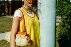 Aria is wearing a striped yellow knit jumper and 70's baguette bag from the shop.