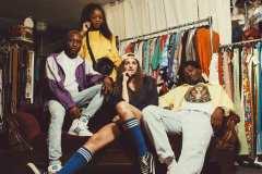 Tahir, wearing 80's purple striped windbreaker, Adidas high-top sneakers. Diane, wearing yellow Nike jersey, Esprit shoulder bag. Andrea, wearing navy sport jersey, knee-high socks. Franklin, wearing 80's denim jeans, USA crew neck sweater, yellow 90's windbreaker.