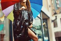 Andrea wearing 80's black vinyl trench coat with matching conductor's hat.