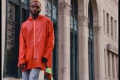 Tahir, wearing 90's red vinyl rain coat, 80's Adidas high-top sneakers.