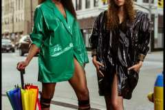 Diane wearing green 80's oversized vinyl blazer. Andrea wearing 80's black vinyl trench coat with matching conductor's hat.