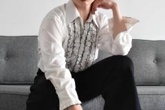 Aidan, wearing a 70's white ruffled tuxedo shirt, black high waisted 70's pants and hat.