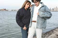 Jack, wearing 80's denim jacket, white Mickey Mouse polo shirt. Grace, wearing 80's high-waist blue jeans, 90's Nautica puffer coat, Batman socks.