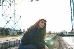 Grace, wearing 80's high-waist blue jeans, 90's Nautica puffer coat, Batman socks.