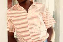 Franklin, wearing powder blue dress pants,50's red and white stripe button up shirt, paired with matching brown leather, blue and white stripe belt.